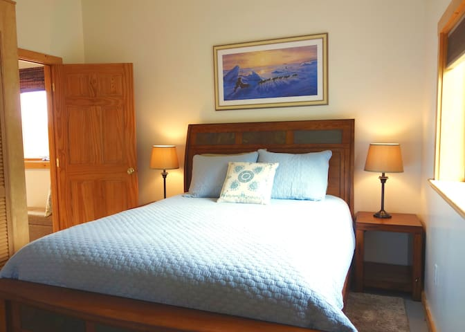 This separate bedroom features a queen bed and room darkening shades for the bright summer months.