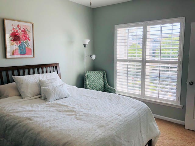 Master Bedroom-Queen size bed, cozy linens, & sitting chair.
