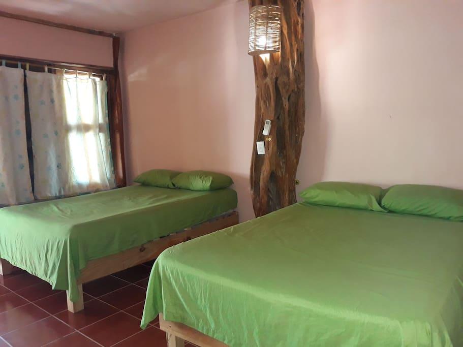 Habitación con dos camas matrimoniales, baño privado y A/A.