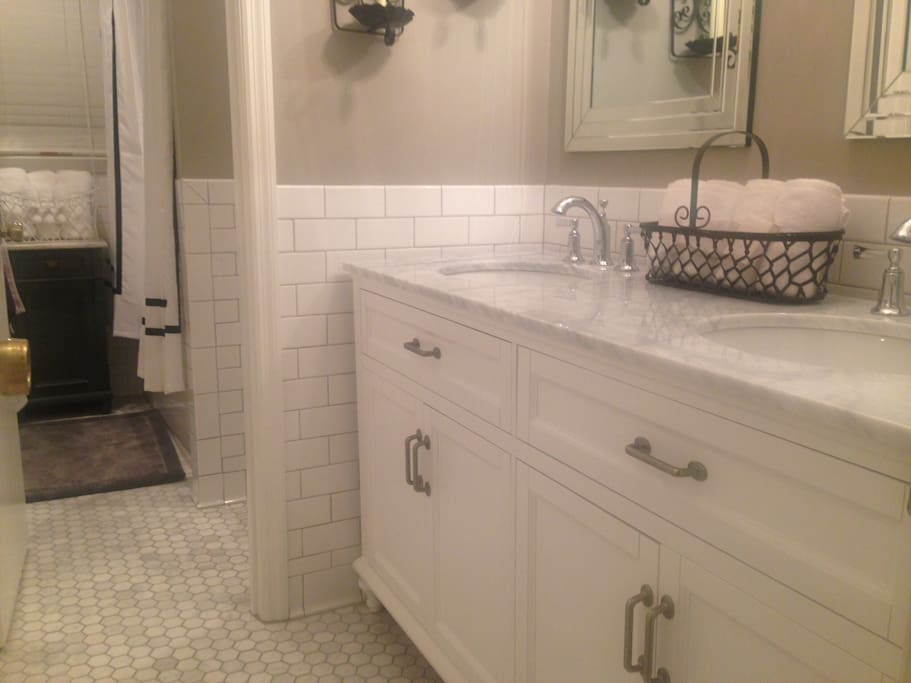{Hallway Bath} Enjoy a 'spa like' experience with carrara marble hexagon tile floors & marble counter tops with chrome lighting & accents throughout! Also subway tile chair rail on all walls -- to the ceiling above spacious shower! Offers  spacious tub!