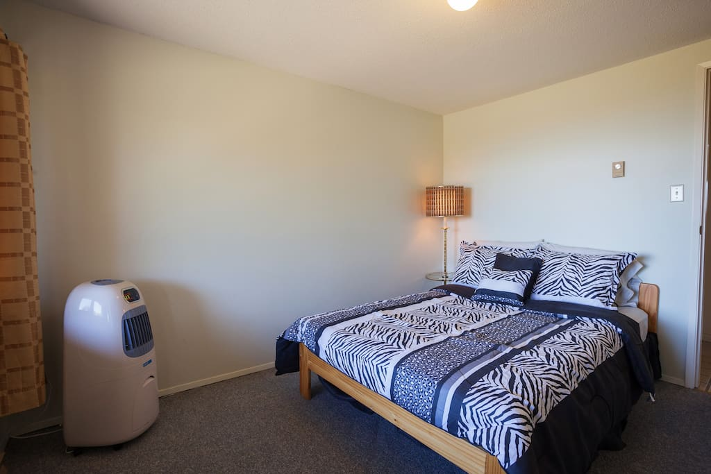 Main bedroom comes with a double bed, stand lamp with attached table & an air cooler