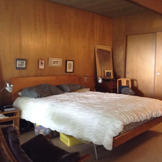 Upstairs Bedroom 1: lined in mahogany paneling; a fully glazed, west-facing wall with sliding glass door opens to balcony over the porch and partial bay view