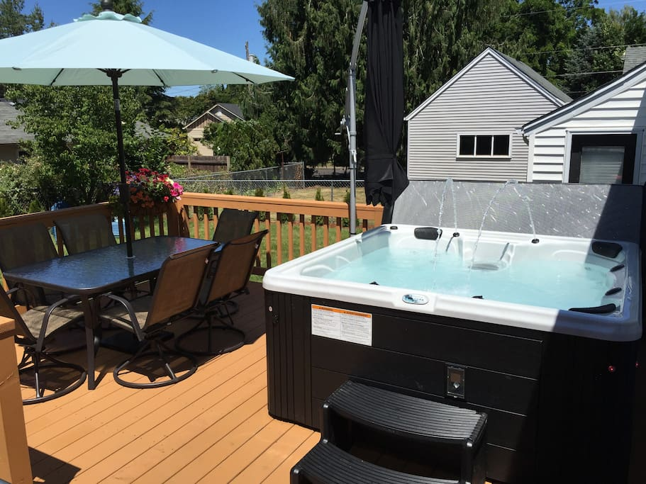 Backyard deck with a 7 person hot tub, deluxe grill and 6 person outdoor table.