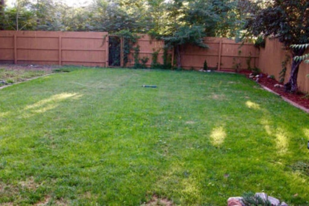 Large back yard with a 6 foot privacy fence, a patio furniture set, and a charcoal grill!