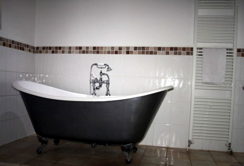 Period bathroom with large double ended roll top bath.