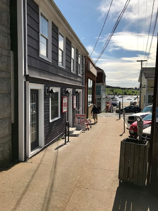 Street level private entrance on the far left. Purple door next to the brass ships bell. Modern luxury awaits upstairs. Lunenburg's harbour is just a block ahead...