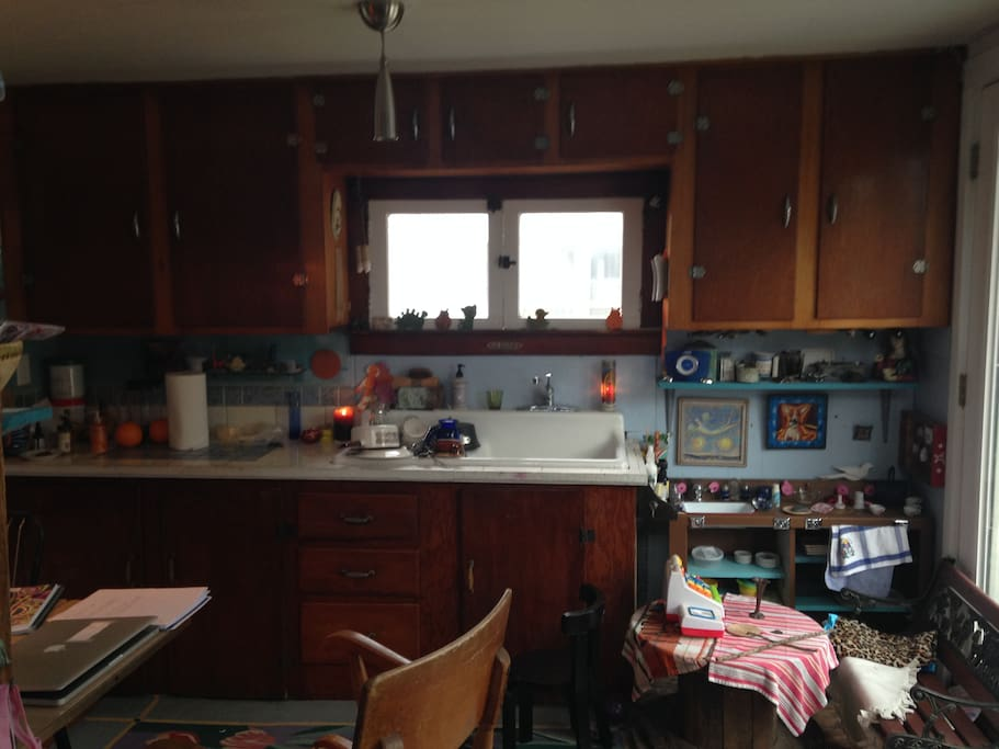Galley Kitchen with eclectic touches.  Farm style sink original windows.  House built by a fisherman before 1900.