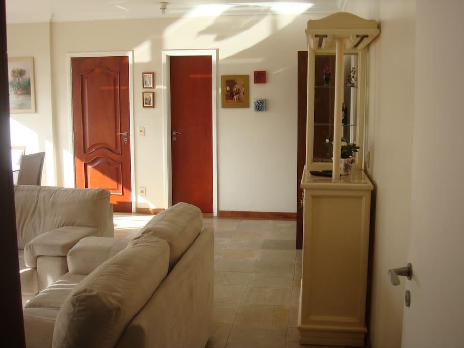 Sala para três ambientes, dois sofás, cristaleira, barzinho, rack, mesa de jantar para seis pessoas, sacada, floreira, vidros grandes com bela vista.