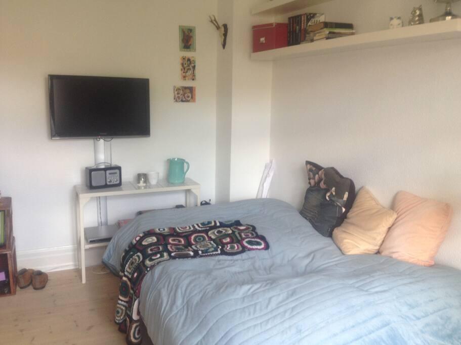 I lejlighedens andet værelse er der seng, tv samt spiseplads til 2-4 personer