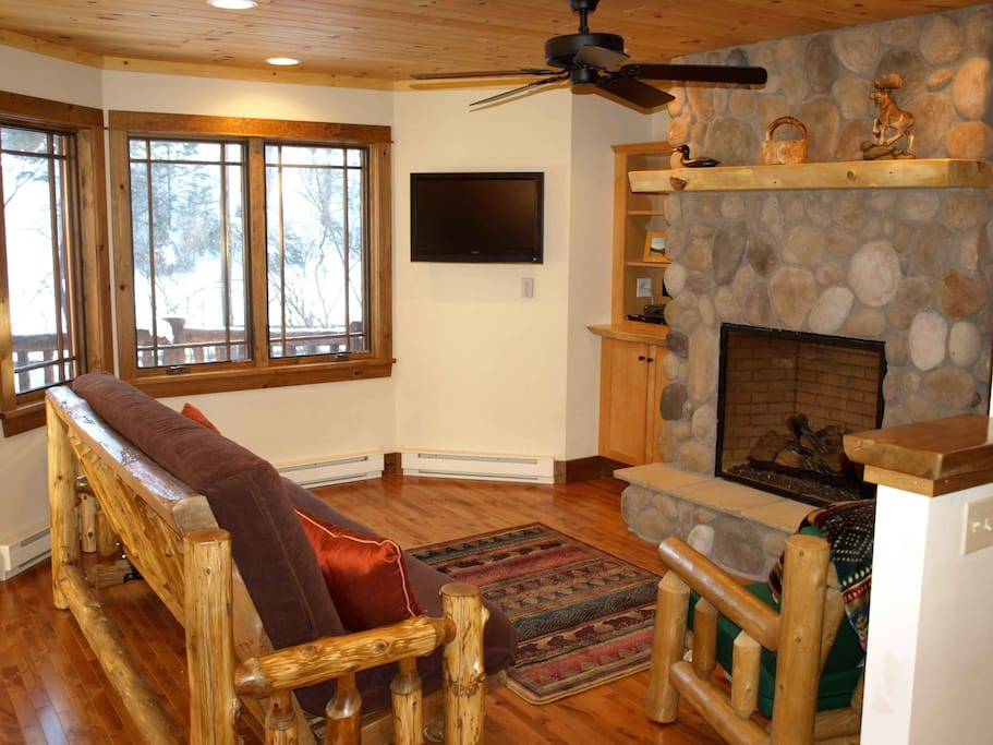 Main level sitting area with river rock fireplace & TV