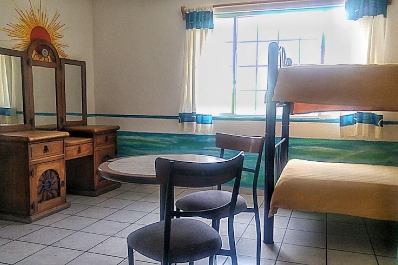 Habitación con 2 literas, tocador, mesita con 2 sillas y baño privado