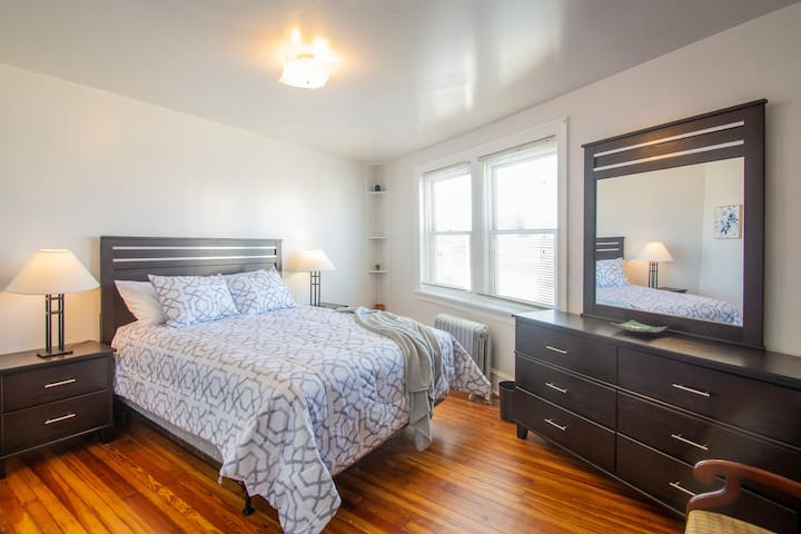 Bedroom #1 features a queen bed and mirrored bureau.