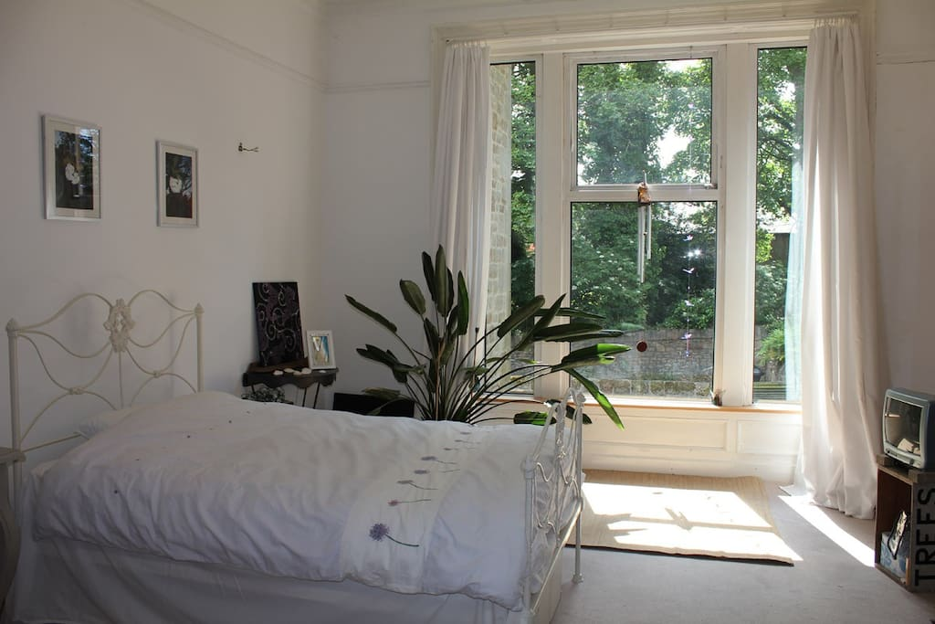 Your bedroom with double bed and view onto garden and trees.