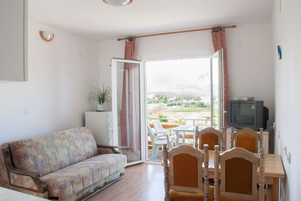 Living room with a pull out sofa (sleeps two), fully equipped kithcen and dining table for up to four persons.