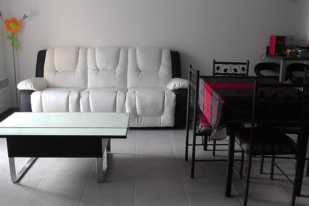 le salon : canapé avec 2 sièges dépliables, table basse dont une partie peut se surélever, table de séjour 117 x 76 cm, TV 140 cm