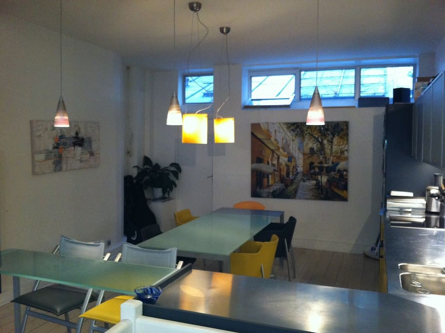 dining area and breakfast bar with modern lighting and artwork