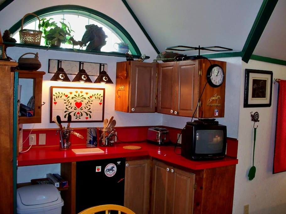 Kitchen area with small fridge, dishes, utensils, toaster, microwave, TV and radio.