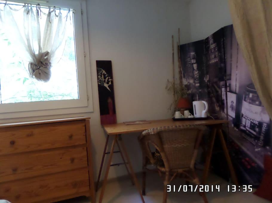 La chambre avec son bureau, sa commande et vue sur le jardin