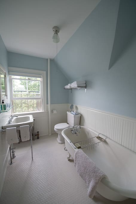 Small, but cozy shared bathroom with antique claw foot tub.