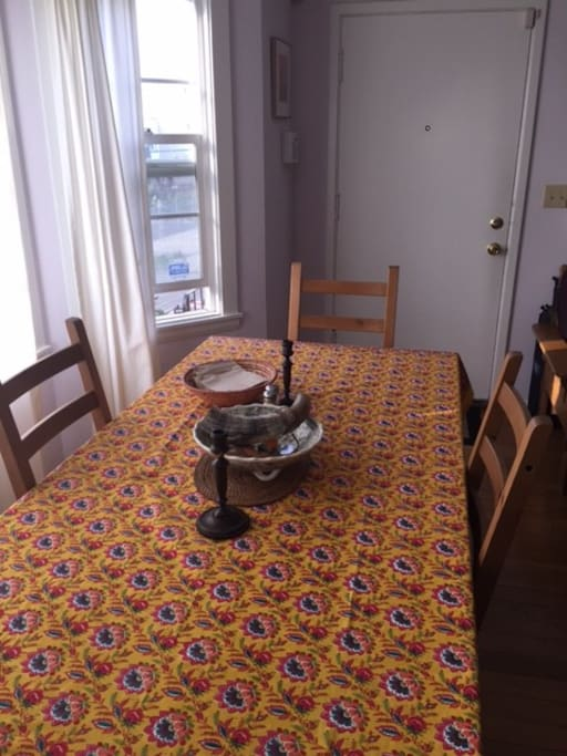 Dining table with sunny bay windows. Seats eight comfortably.