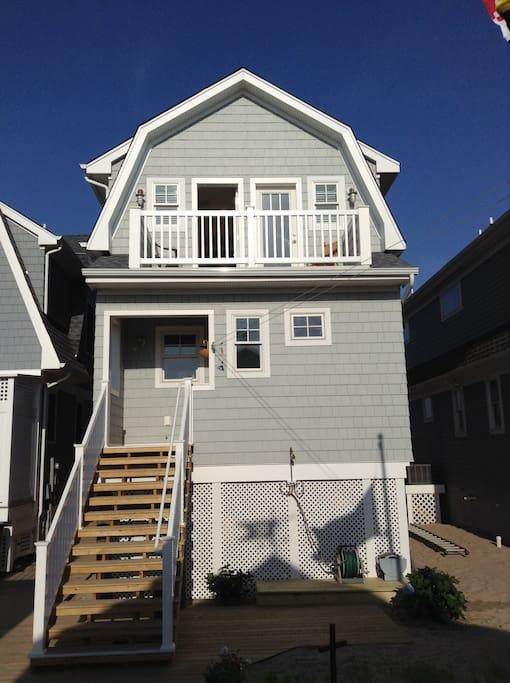 Back of house, includes grill, outside shower, beach chairs.