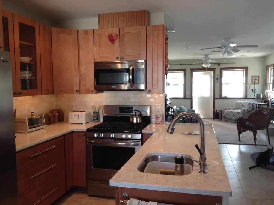 Kitchen looking into living area; quartz counters; ss appliances
