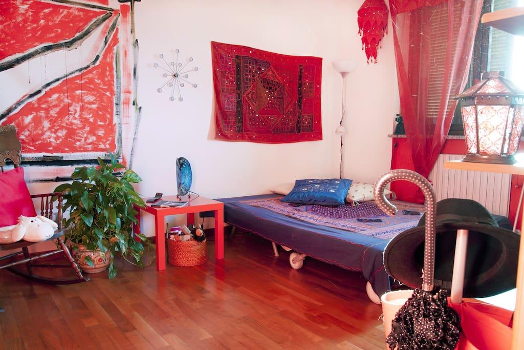 La stanza rossa con il divano letto e le decorazioni artistiche degli amici che hanno soggiornato qui. Ogni pezzo, una storia