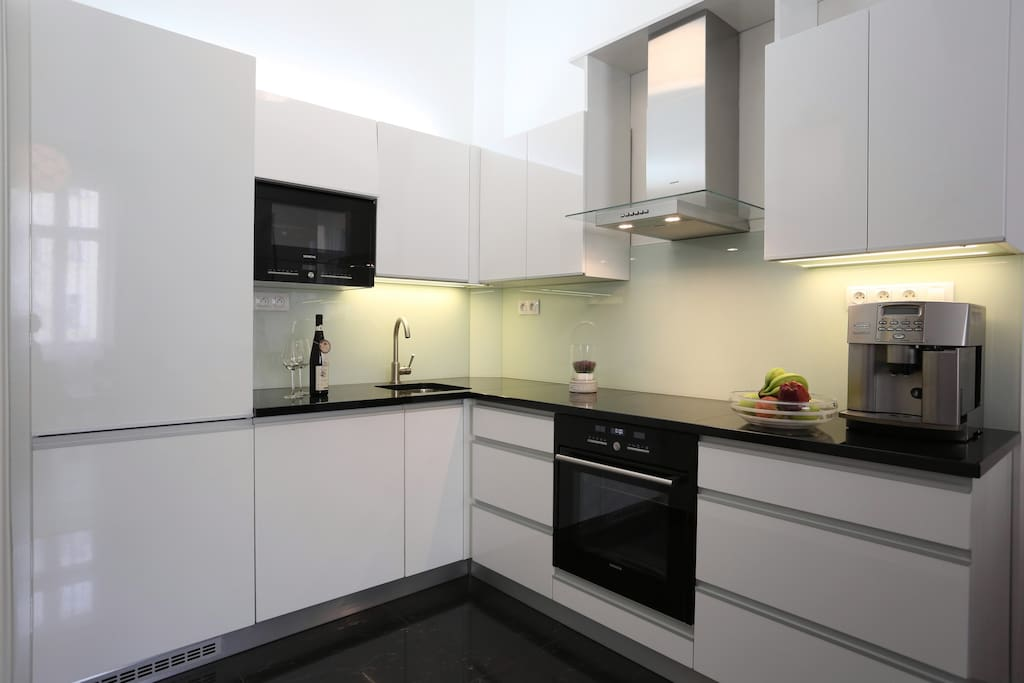 kitchen with electric stove, plates, dishes, silverware, microwave, coffee maker, kettle, fridge, dishwasher