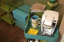Desk, with mini-fridge and coffee cart.