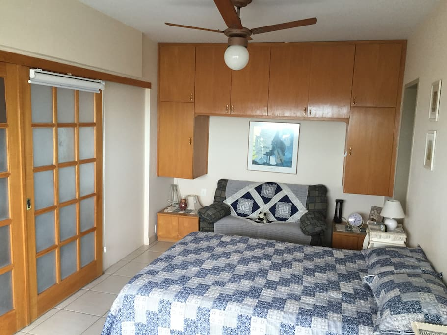 bedroom with queen bed, sofa bed, remote control fan, split air conditioning and private bathroom
