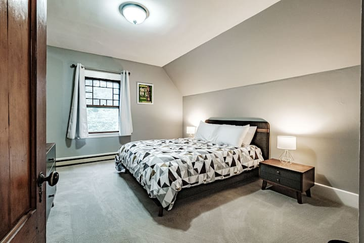 Third floor bedroom with one queen bed.
