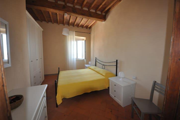La camera matrimoniale è arredata con un armadio capiente, una cassettiera, un letto in ferro battuto e due comodini. Conserva la bellezza dei travi in legno e del pavimento in cotto toscano.