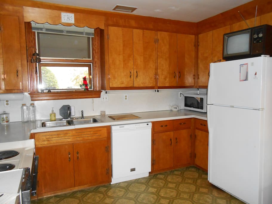 Kitchen with double oven, dishwasher, microwave, refrigerator, TV and kitchen table with four chairs over looking the back yard and lake
