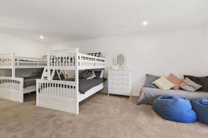 Bedroom 2 - large room with two single over double bunk beds, quality mattresses & bedding. TV/play area with ottoman/daybed & beanbags.