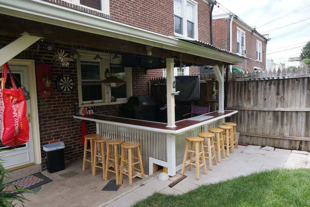 Covered backyard patio with a built in 12 ft. L shaped bar and gorgeous lawn with landscaping