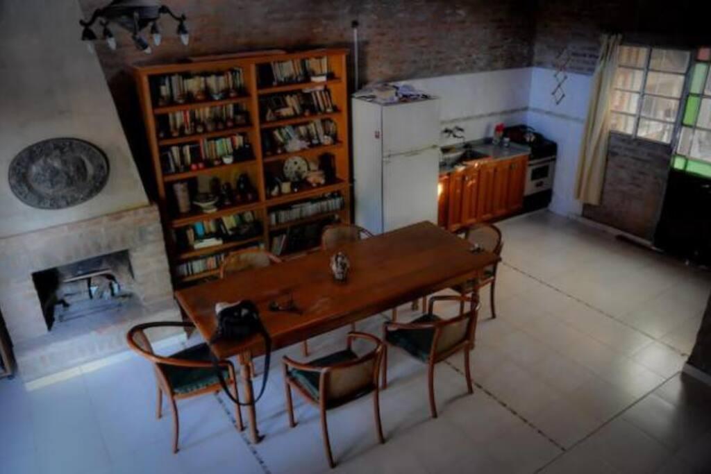 Espacio común tipo cocina comedor living con televisión, chimenea y sofá