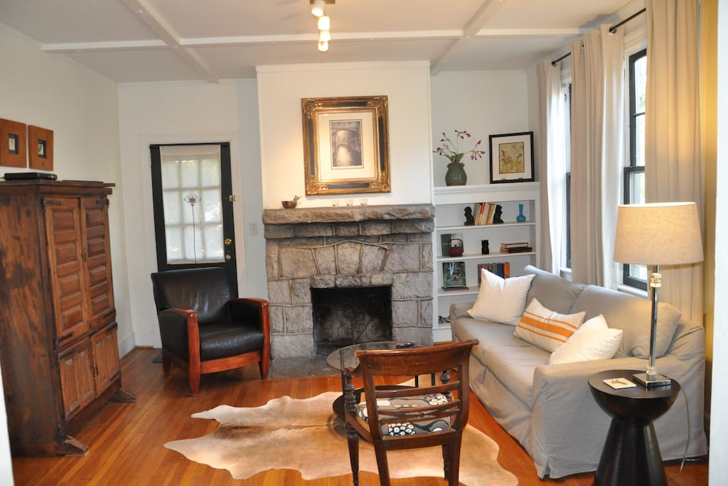 Living room with original granite fireplace and Mitchell-Gold sleeper sofa.