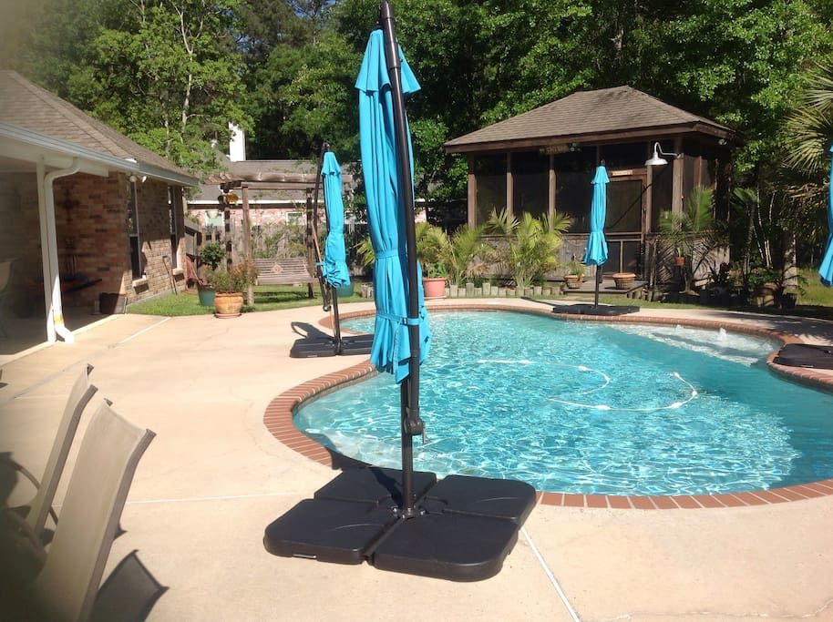Additional umbrella table & 6 chairs on pool deck, & wooden swing