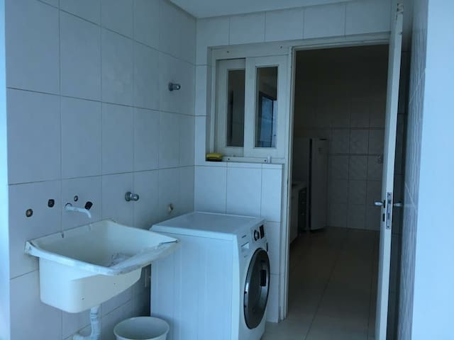 Lavanderia, máquina de lavar e secar e tanque auxiliar.