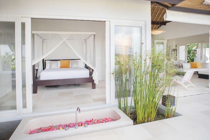 The master bedroom with flower petal outdoor bathtub surrounded by ornamental fishpond