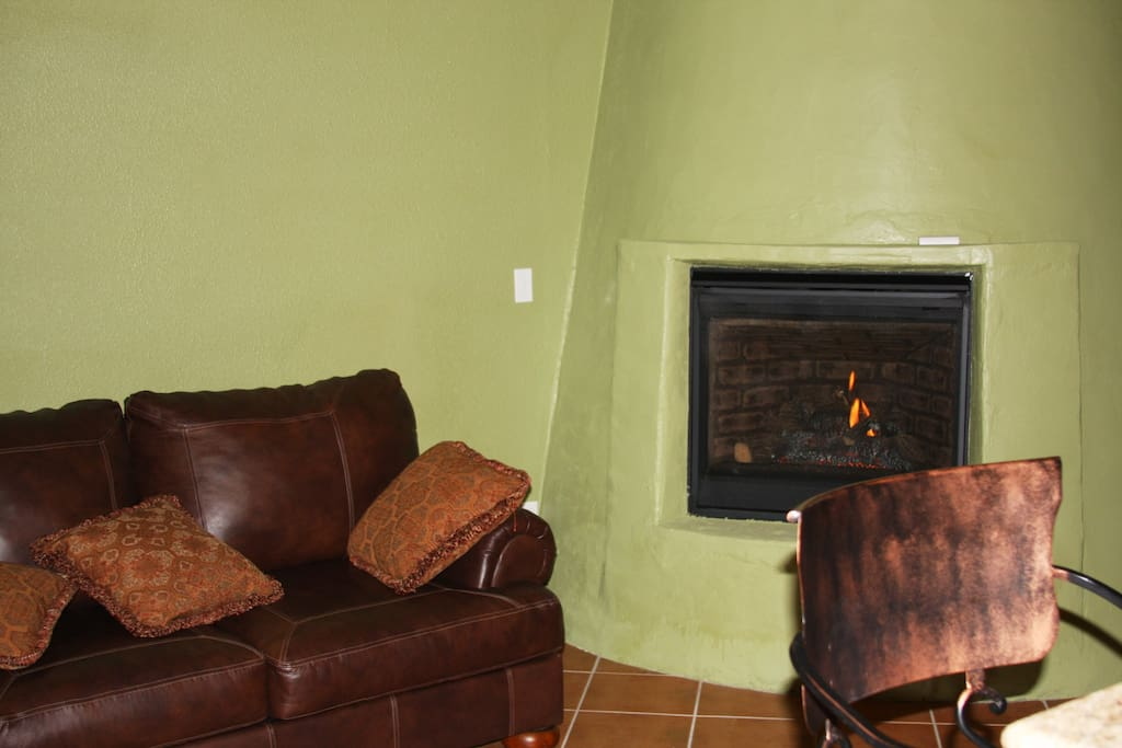 Fireplace, huge comfortable leather couch, copper back swivel chairs.