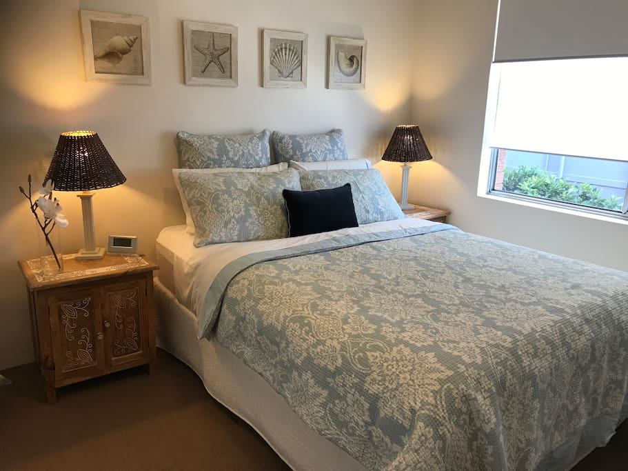 Master bedroom with partial ocean views, ceiling fan, built in wardrobe and queen bed.