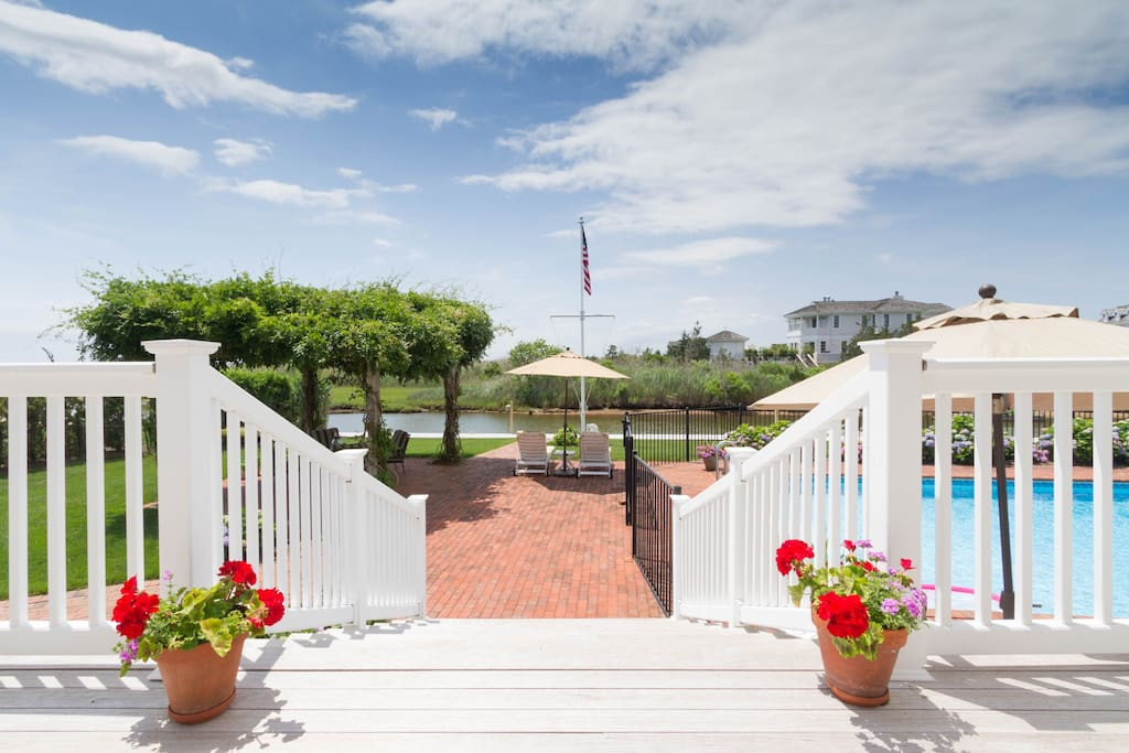 """Stairs leading to the backyard patio, wisteria covered arbor, pool and boat dock. """"Amazing views on the bay, which makes it hard to leave the house once you're there."""""""