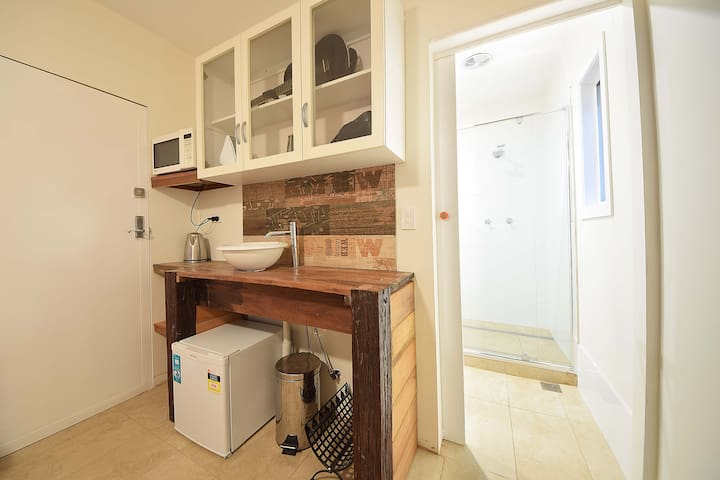 kitchenette with small refrigerator/freezer, microwave, sandwich maker and kettle.  Crockery and cutlery for 2.