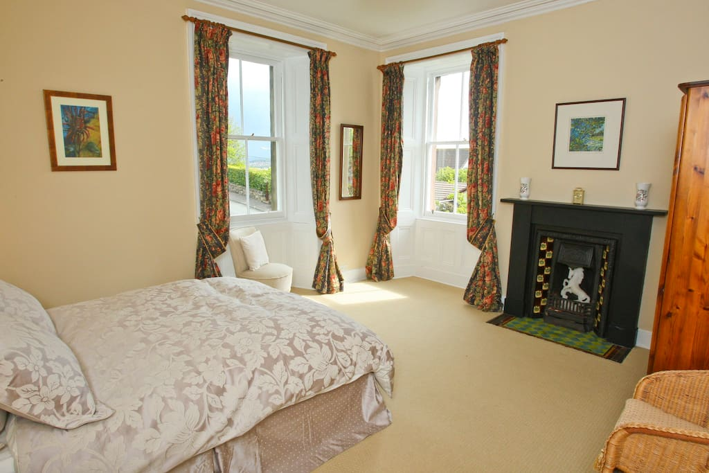 Spacious double bedroom, original features bathed in morning light.