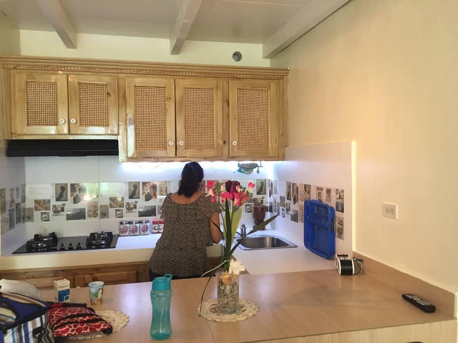Cocina completa con su estufa empostrada, tostadoras, microonda, greca, nevera y dispensador de agua, etc.
