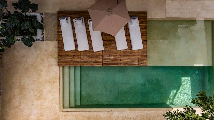 Cuartos amueblados en un espacio verde con piscina