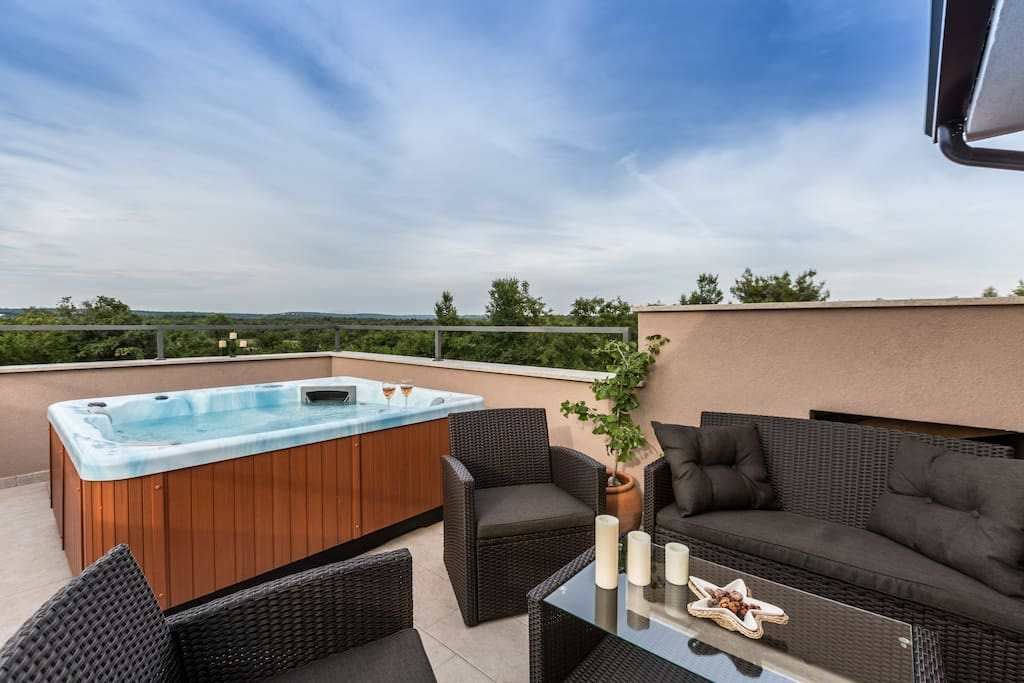 Relax area on terrace with whirlpool and a look to the forest and the vineyards around the house