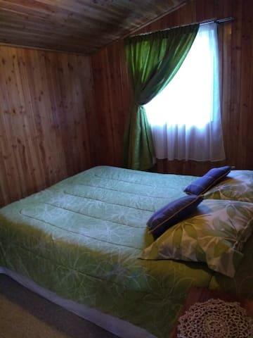 Habitación matrimionial con vistas al jardín. Existe la posibilidad de añadir una cama supletoria a la cabaña.