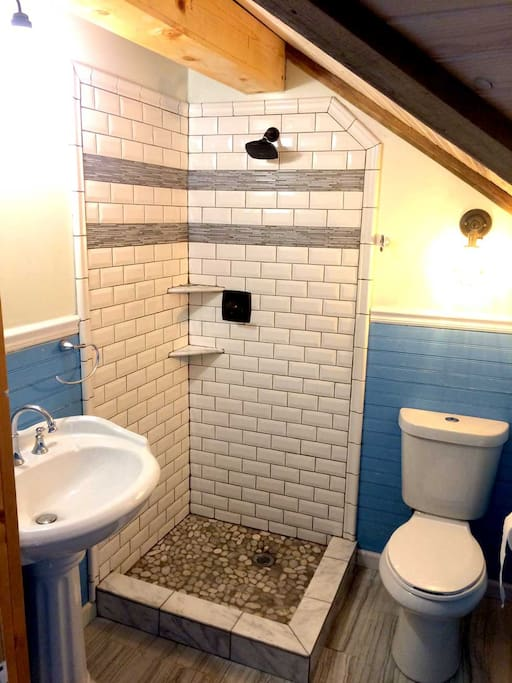 Private brand-new bathroom attached to the room, custom beveled tiled shower, exposed beams, beautiful tile floor
